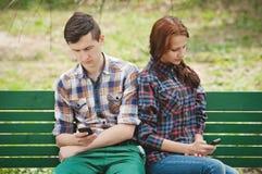 Un par que mira cada uno en su teléfono móvil Fotografía de archivo