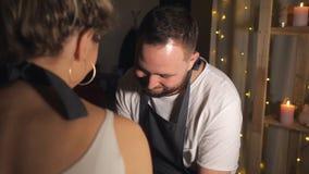 Un par que mira uno a y tactos de la muchacha la nariz del hombre con un finger sucio en taller de la arcilla almacen de metraje de vídeo