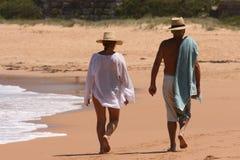 Un par que recorre a lo largo de una playa Imágenes de archivo libres de regalías