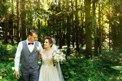 Un par que se casa goza el caminar en el bosque Recienes casados abrazar y llevar a cabo las manos foto de archivo libre de regalías