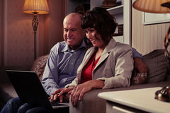 Un par que se sienta en el sofá que mira algo en un ordenador portátil Imágenes de archivo libres de regalías