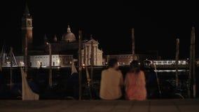 Un par que se sienta en el terraplén delante de la opinión de Venecia de la noche almacen de metraje de vídeo