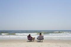 Un par que se sienta en sillas de la lona Fotos de archivo libres de regalías