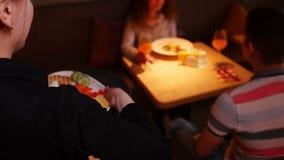 Un par que se sienta por la tabla en un café El camarero viene a ellos y trae el plato almacen de metraje de vídeo