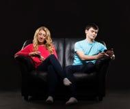 Un par que se sienta por separado con smartphones Fotografía de archivo