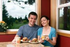 Un par que sonríe sobre el desayuno en el país Imágenes de archivo libres de regalías