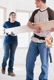 Un par que sostiene un tablón de la madera imagen de archivo libre de regalías