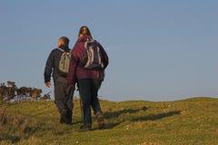 Un par que va de excursión a través del campo Fotos de archivo