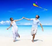 Un par que vuela una cometa en la playa Imágenes de archivo libres de regalías
