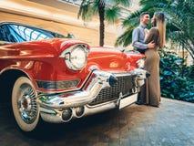 Un par romántico está haciendo una pausa el coche rojo Un hombre está abrazando a una mujer Obras clásicas americanas El individu imágenes de archivo libres de regalías
