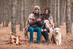 Un par se está sentando en un bosque con un Labrador, bebiendo el té cubierto en manta y la risa outdoors imagenes de archivo