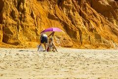 Un par se sienta en la sombra de un paraguas en la playa de Falesia en Portugal foto de archivo libre de regalías