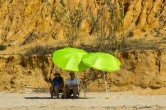 Un par se sienta en la sombra de un paraguas en una playa en Portugal fotos de archivo