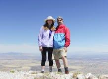 Un par sonriente en un pico de montaña Foto de archivo libre de regalías