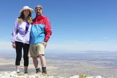 Un par sonriente en un pico de montaña Foto de archivo