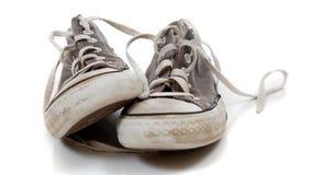 Un par usadas de zapatillas de deporte grises en un fondo blanco Imagen de archivo