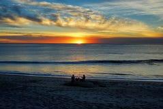 Un par y su perro que se sientan en la playa que disfruta de una puesta del sol a lo largo de la costa del Condado de Orange Imagenes de archivo