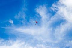 Un paracadutista solo nel cielo blu Fotografia Stock