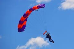 Un parachutisme de exécution de parachutiste avec le ciel bleu à l'arrière-plan images libres de droits