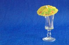 Un paraguas amarillo del cóctel exhibido con un vidrio vacío de la pistola Foto de archivo