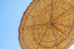 Un paraguas de sol de lámina y un cielo azul que simbolizan vacationing en el summ Fotos de archivo libres de regalías