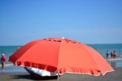 Un paraguas rojo abierto en la playa fotos de archivo