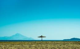 Un paraguas solitario en la playa arenosa Fotografía de archivo