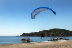 Un parapendio entra atterrare sulla spiaggia di Oludeniz sulla costa del turchese della Turchia immagini stock