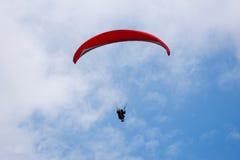Un parapentiste dans le ciel bleu avec le parachute rouge glissant pour l'amusement et l'excitation photographie stock libre de droits