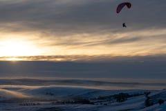 Un parapentiste effectuant le vol au milieu de l'hiver contre le coucher du soleil image stock