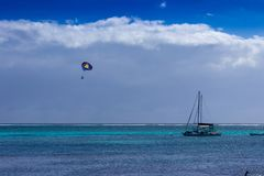 Un parasail flotte au-dessus des eaux bleues et azurées de la mer des Caraïbes de la côte de Belize image libre de droits