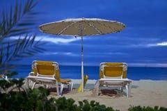 Un parasol et deux lits de plage Images libres de droits