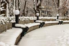 Un parc en hiver Les bancs sous la neige dans une récréation se garent Images libres de droits