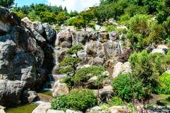 Un parco con acqua che cade dalle rocce fotografia stock