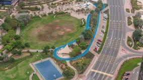 Un parco pubblico abbellito nel timelapse delle torri dei laghi Jumeirah, un distretto residenziale popolare nel Dubai archivi video