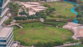 Un parco pubblico abbellito nel timelapse delle torri dei laghi Jumeirah, un distretto residenziale popolare nel Dubai video d archivio