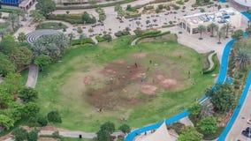 Un parque público ajardinado en timelapse de las torres de los lagos Jumeirah, un distrito residencial popular en Dubai almacen de metraje de vídeo