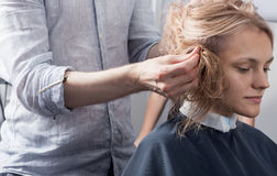 Un parrucchiere che fa un taglio di capelli per un cliente femminile biondo Fotografie Stock