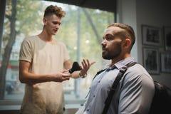 Un parrucchiere di visita dell'uomo serio in un parrucchiere Un barbiere che prepara gli strumenti per una rasatura su un fondo d fotografia stock