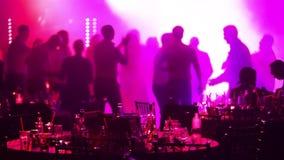 Un partido de la juventud en un restaurante o un club nocturno, tablas de banquete con alcohol y comida contra la perspectiva de  metrajes
