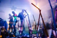 Un partido en un club nocturno, vidrios del champán con la paja Fotografía de archivo