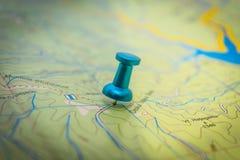 Un pasador azul integrado en el mapa Foto de archivo