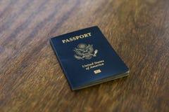 Un pasaporte americano azul encima de un escritorio de madera imagen de archivo