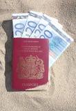 Un pasaporte británico y euros. Foto de archivo