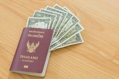 Un pasaporte tailandés de los billetes de dólar Imagenes de archivo