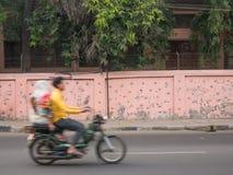 Un paseo del hombre su bici con una mujer detrás de él fotos de archivo libres de regalías