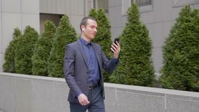 Un paseo joven del hombre de negocios con los auriculares inal?mbricos en sus o?dos y el hablar en una llamada video en smartphon