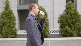 Un paseo joven y ventajas del hombre de negocios una conversaci?n del negocio sobre los auriculares inal?mbricos en sus o?dos