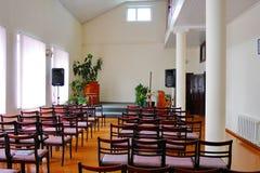 Un pasillo acogedor en un cuarto con los altos techos y las paredes blancas con filas de sillas y una etapa con los altavoces de  fotos de archivo libres de regalías