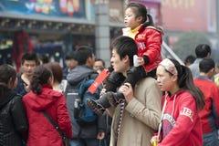 Un paso feliz de la familia a través de una calle muy transitada Foto de archivo libre de regalías